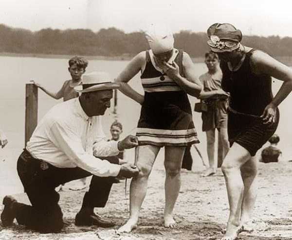 23.) Beach patrols measuring the length of women's bathing suits in the 1920s.