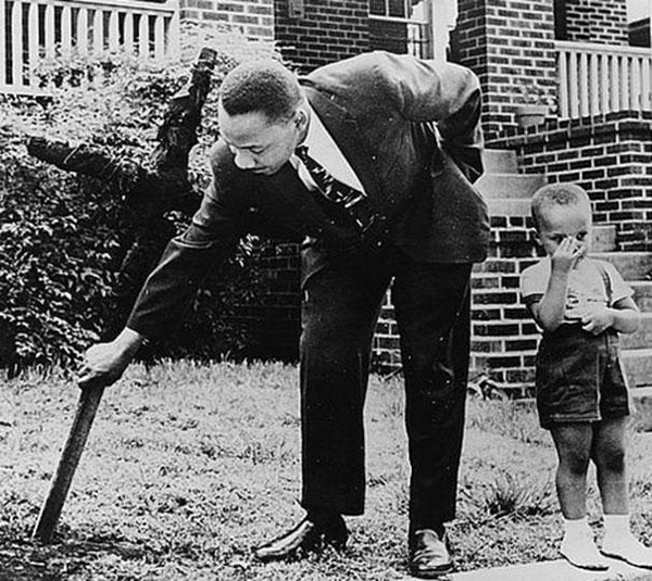 24.) Martin Luther King Jr. removing a burned cross from his yard with his son in 1960.