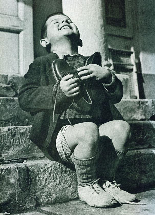 30.) A joyful Austrian boy receives new shoes during WWII.