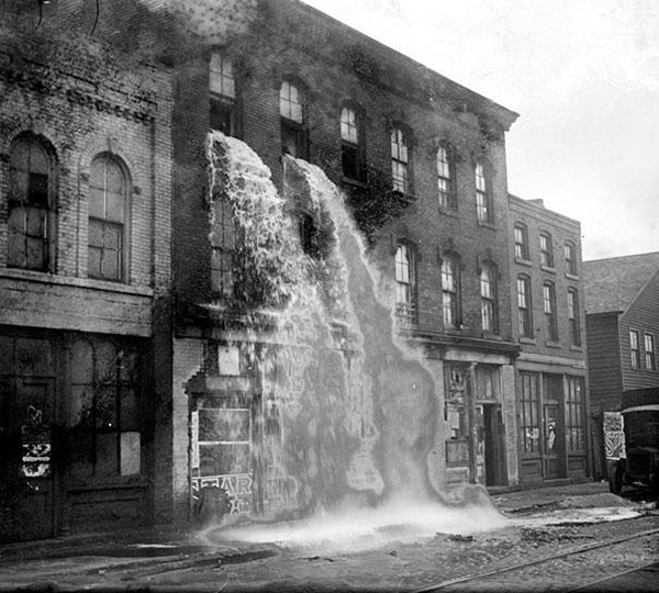 37.) Alcohol being poured out on the streets during Prohibition Detroit in 1929.